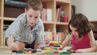 Two kids playing with lego bricks at home