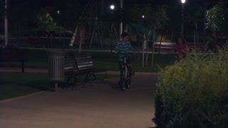 Two kids riding thier bike in a park at night
