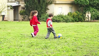 Two young kids playing with a ball in slow motion outdoors