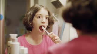 young girl brushing her teeth in front of the mirror