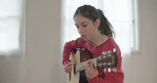young girl trying to play guitar, having problems