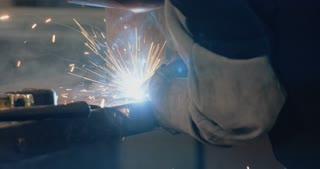 Welder welding metal parts in a workshop