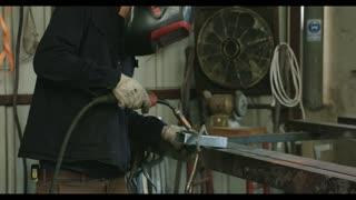 Welder welding metal parts in workshop