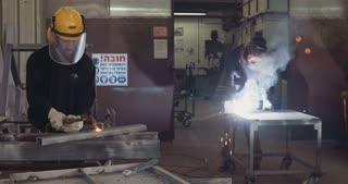 welders cut metal and weld in a workshop