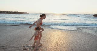 Woman and her daughter running on the beach during sunset