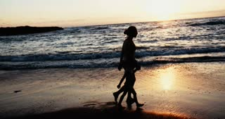 Woman and little girl walking on the beach during sunset