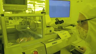 Worker inspecting silicon wafer in a Semiconductor manufacturing facility
