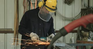 worker working with a metal grinder in a workshop