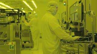 Workers in clean suits in a Semiconductor manufacturing facility