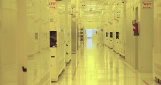 Workers in clean suits in a semiconductor productions facility