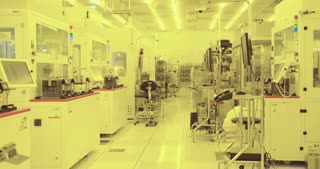Workers in clean suits on a production floor in a semiconductor fabrication facility