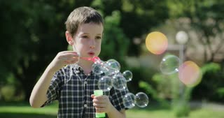 young boy blowing soap bubbles in the sun