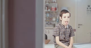 young boy getting his throat checked by a female doctor