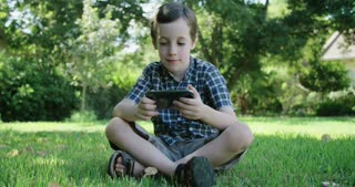 young boy playing with a mobile phone sitting on the lawn outdoors
