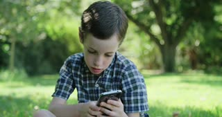 young boy playing with a mobile phone sitting outside