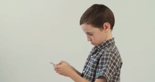 Young boy plays with a smartphone