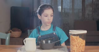 young girl eating cereal with milk