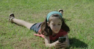 young girl playing with a mobile phone laying on the grass