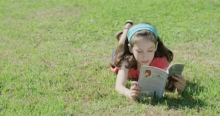young girl reading a book laying in the sun