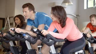 A spinning class on exercise bikes at a gym