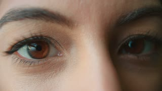 A woman�s brown eyes blinking and creasing to smile, detail