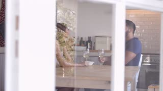 Adult couple sit drinking wine in kitchen and make a toast, shot on R3D