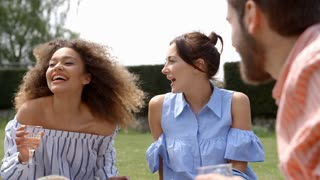 Adult friends talking at a picnic on a breezy day, close up