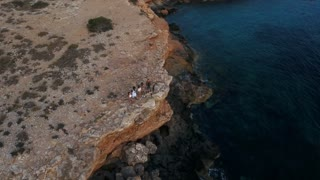 Aerial Shot Of Friends On Cliffs Watching Sun Set Over Sea