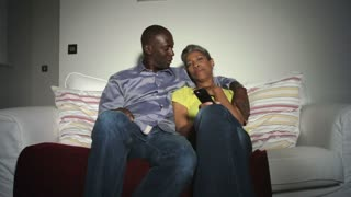 African American Couple On Sofa Arguing Over TV Remote