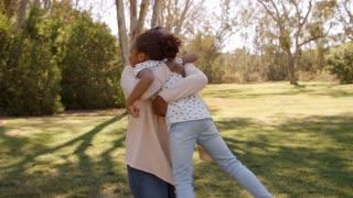 African American grandma lifting her granddaughter in park