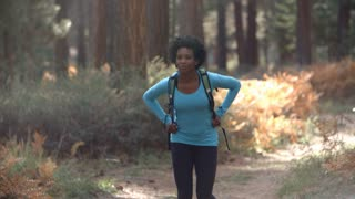 African American woman running in a forest with a backpack