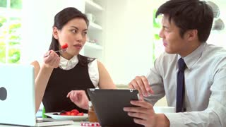 Asian Couple Using Laptop And Digital Tablet Over Breakfast