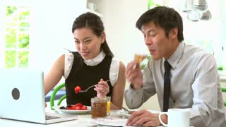 Asian Couple With Laptop And Newspaper At Breakfast