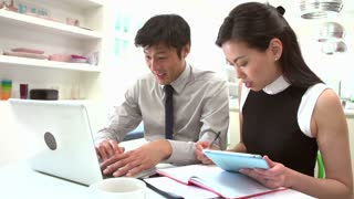 Asian Couple Working From Home Looking At Personal Finances