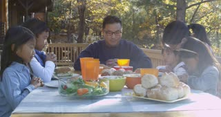 Asian family at a table on a deck say a prayer before eating, shot on R3D