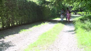 Asian Family Enjoying Walk In Countryside