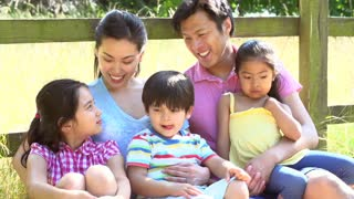 Asian Family Relaxing By Fence On Walk In Countryside