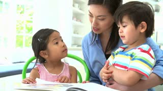 Asian Mother Reading A Story To Children