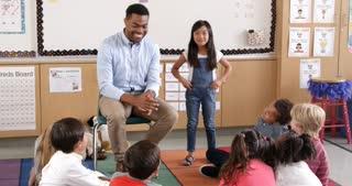 Asian schoolgirl standing with teacher in front of class