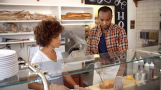 Black couple working behind the counter at a sandwich bar