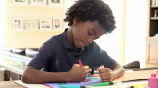 Boy Drawing Picture On Table At Home