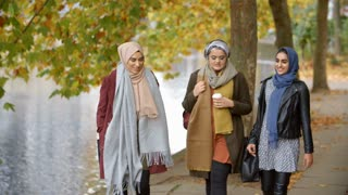 British Muslim Female Friends Walking By River In City