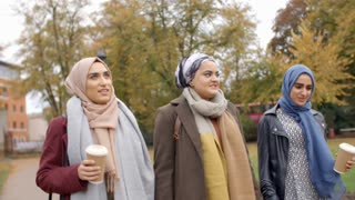 British Muslim Female Friends Walking Through City Park