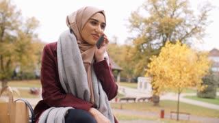British Muslim Woman On Break Using Mobile Phone In Park
