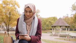 British Muslim Woman Texting On Mobile Phone In Park