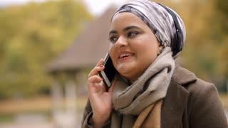 British Muslim Woman Using Mobile Phone In Park
