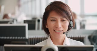 Chinese woman working in a call centre using a headset