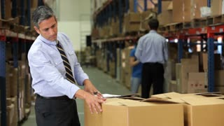 Businessman Checking Box Detail With Clipboard