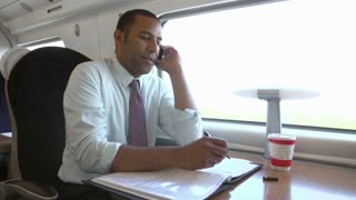 Businessman Commuting To Work On Train Using Mobile Phone