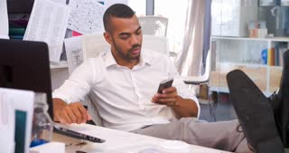 Businessman In Office At Desk Talking On Mobile Phone